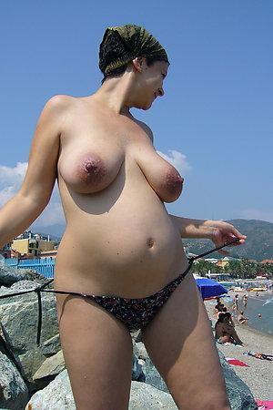 Topless pregnant women on sunny beach