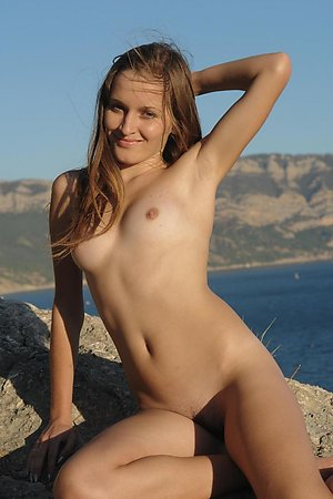 Sweet young girl exposing her boobs and tight pussy on the rocks